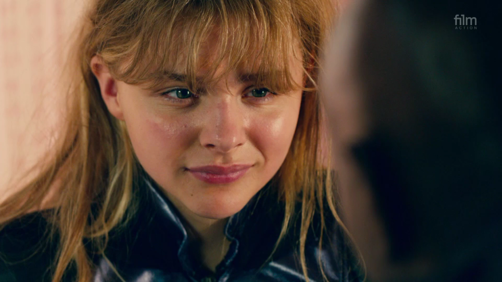 Close up of Chloë Grace Moretz as Hit Girl in Kick Ass 2, talking to her guardian Marcus