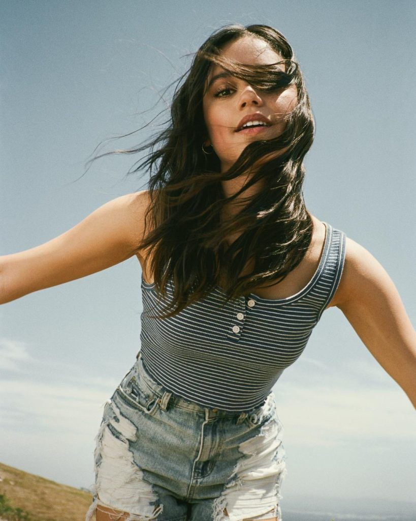 Jenna leaning forward, wind blowing through her hair, wearing a blue-white striped top and worn jeans.