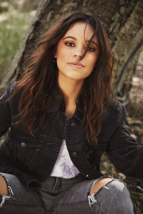Jenna sitting in front of a tree, wearing a black jeans jacket over a  white shirt and matching dark jeans, a strand of hair falls down over her face